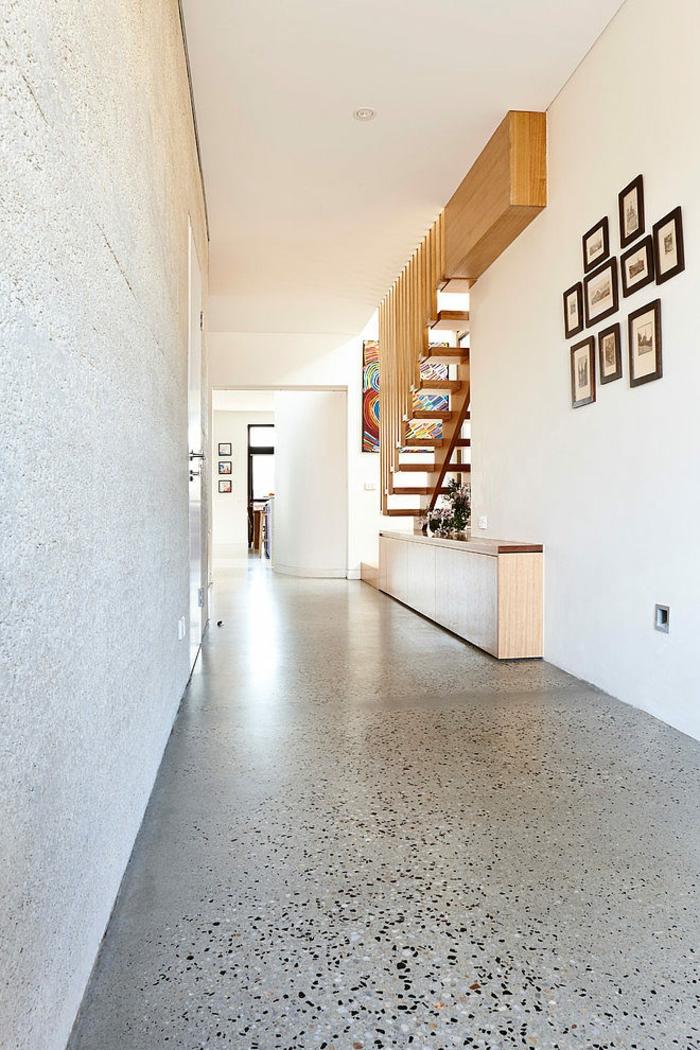 escalier moderne escalier bois fixé sur un mur blanc, avec sol brillant en noir et blanc, neuf tableaux petits et grands au cadre en noir au mur, plafond blanc