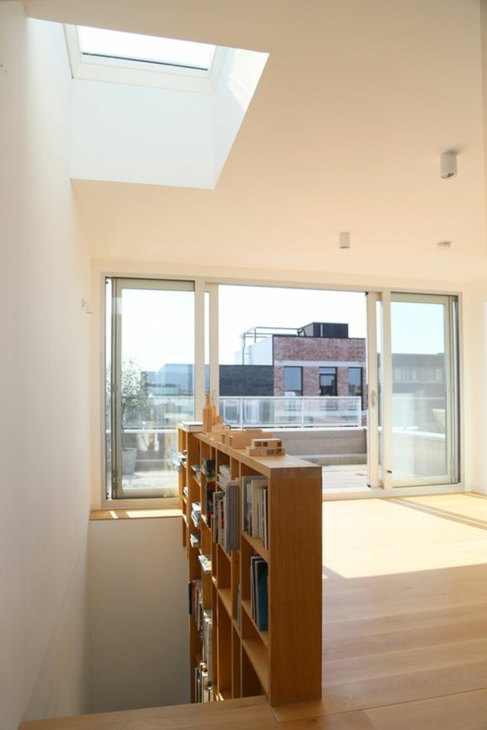 escalier bois escalier moderne escalier design en bois clair avec étagères bibliothèque insérées, maisonnette avec étage supérieur très lumineux, plafond avec fenêtre carrée et une fenêtre avec portes coulissantes pour sortir sur le toit