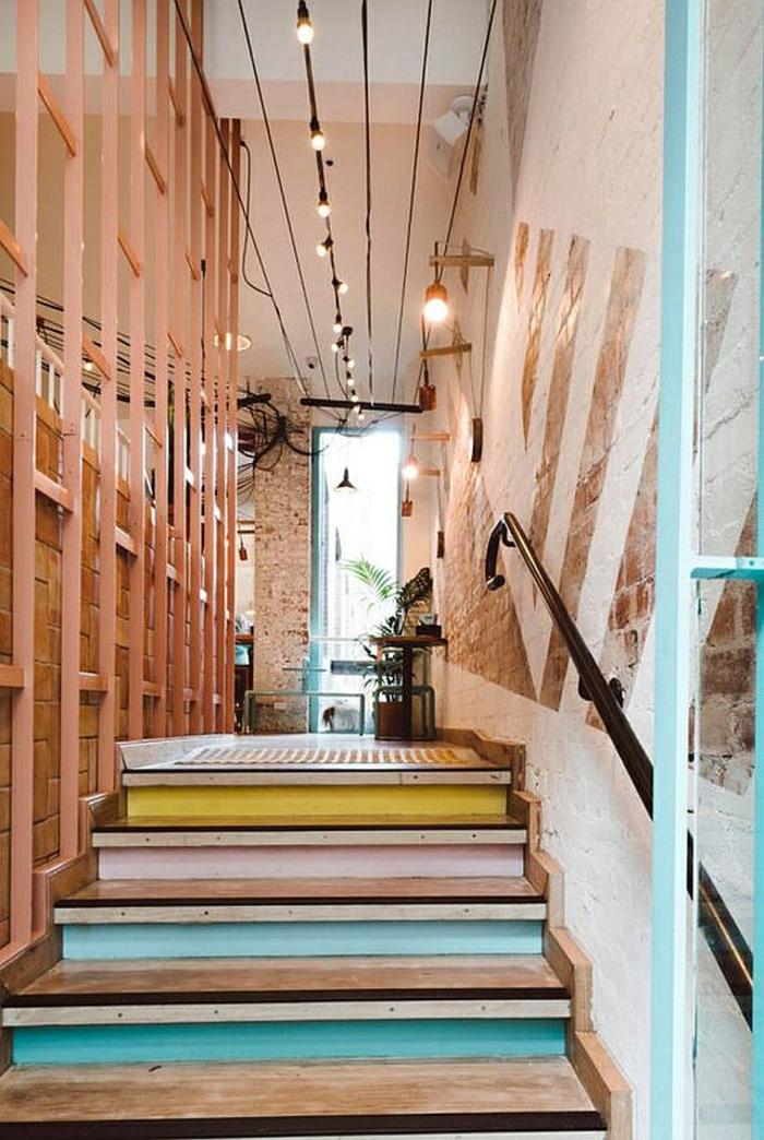 escalier design avec les marches en couleurs gaies, jaune, rose et bleu turquoise, avec guirlande au fil noir avec des ampoules lumineuses suspendues au-dessus de l'escalier