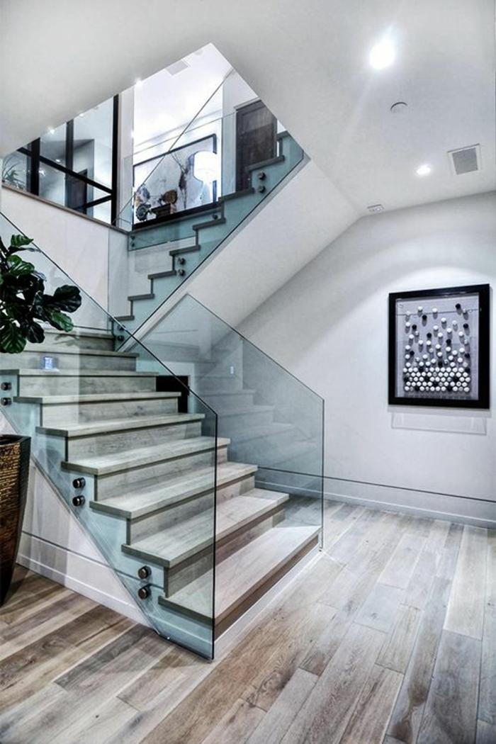 garde corps escalier interieur en verre transparent nuance bleutée, parquet couleur grise et taupe, tableau art style avant-garde au cadre noir avec des boules de couleurs diverses, espace très lumineux