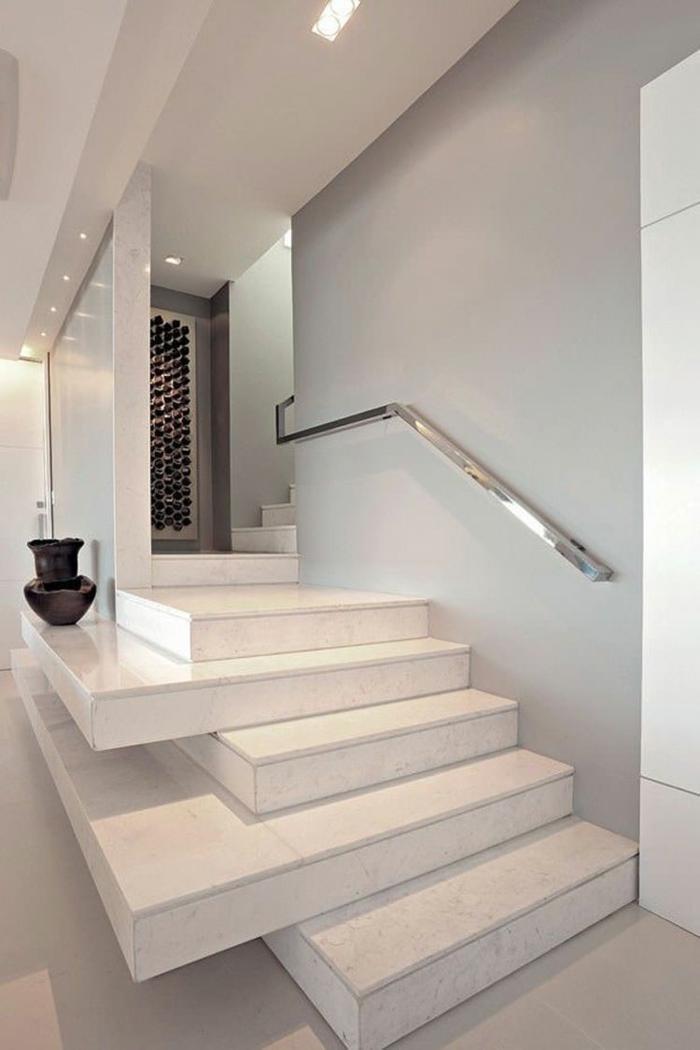 escalier design avec des marches en blanc disposées en manière irrégulière, certaines dépassant les autres, avec poignée fixée sur le mur en couleur argent luisant, grand vase décoratif en noir sur l'une des marches
