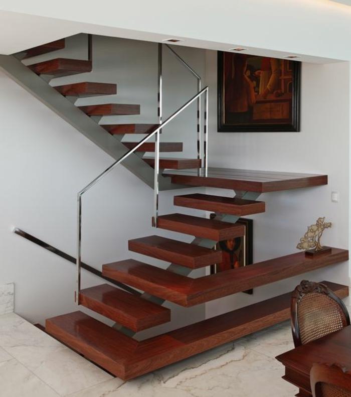 escalier bois avec des marches en couleur cerise, garde corps escalier interieur en métal couleur argent, sol recouvert de carrelage aux motifs marbrés, table et chaises en couleur cerise