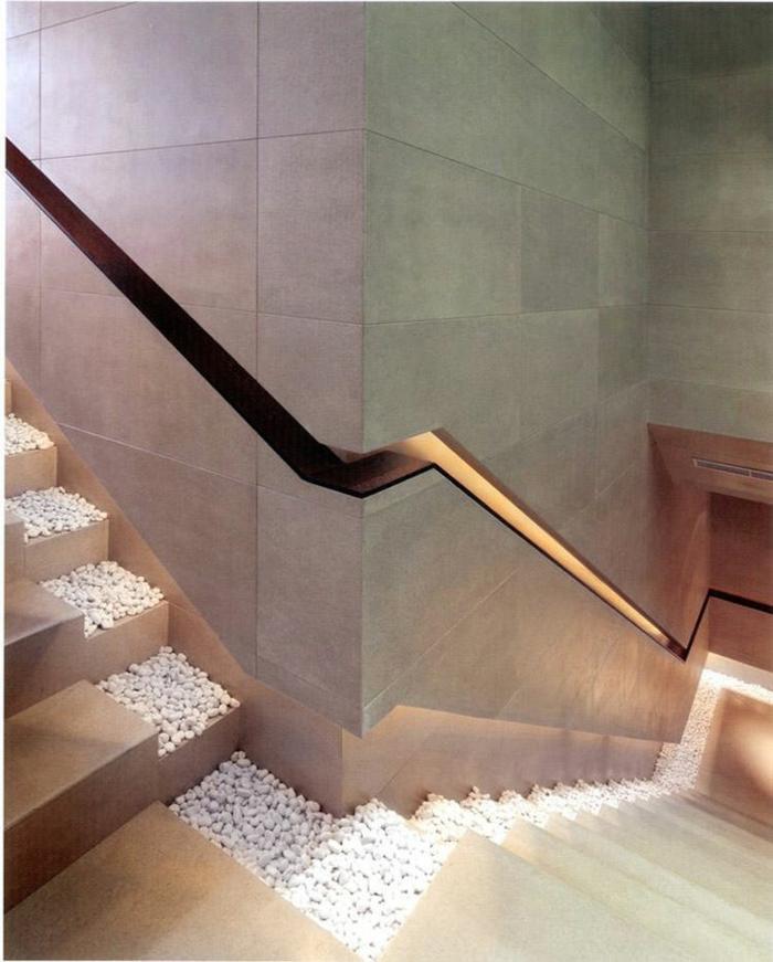 escalier bois clair avec des marches partiellement remplies de petits cailloux blancs décoratifs, poignée en couleur bronze, escalier illuminé par des petits points lumineux discrets