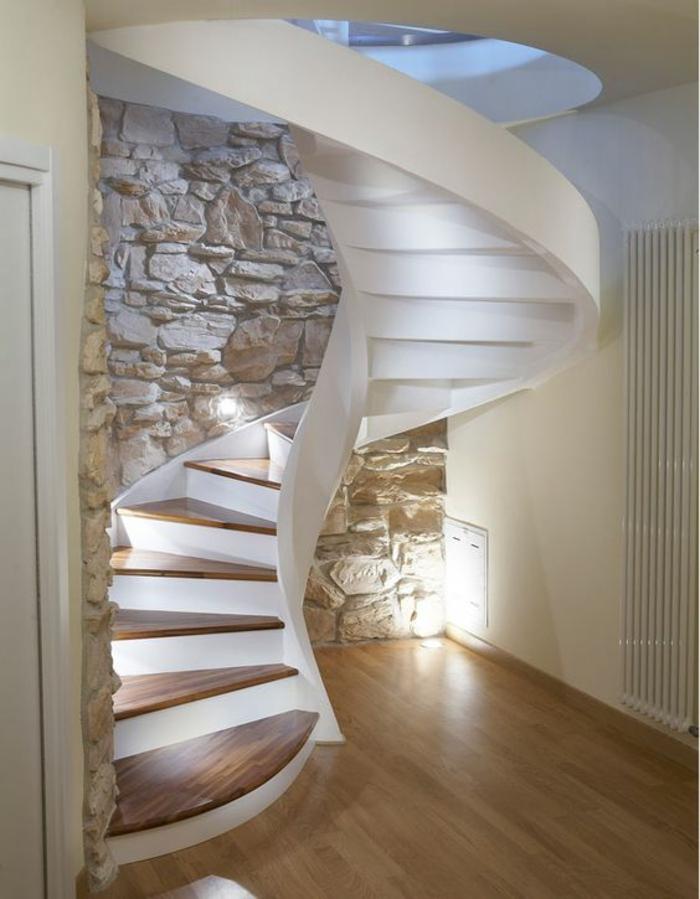 escalier moderne en blanc spirale sur un mur en cailloux rocheux décoratifs, sol revêtu de parquet PVC imitation bois clair