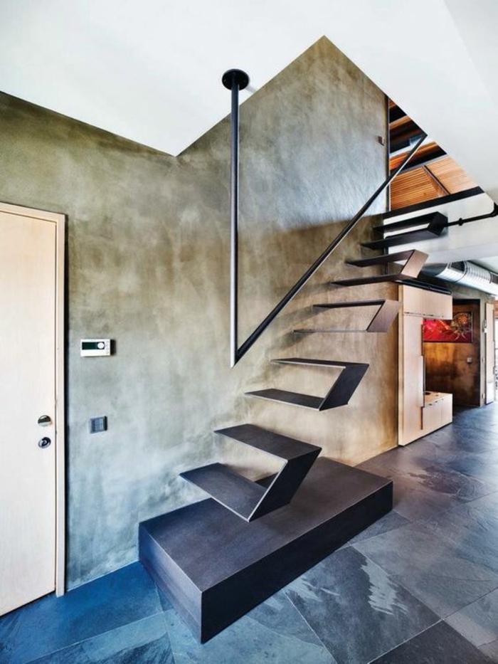 escalier moderne en métal noir avec base solide, marches suspendues sans garde corps, poignée noire en métal, murs gris, sol avec carrelage en nuances noires, grises et blanches