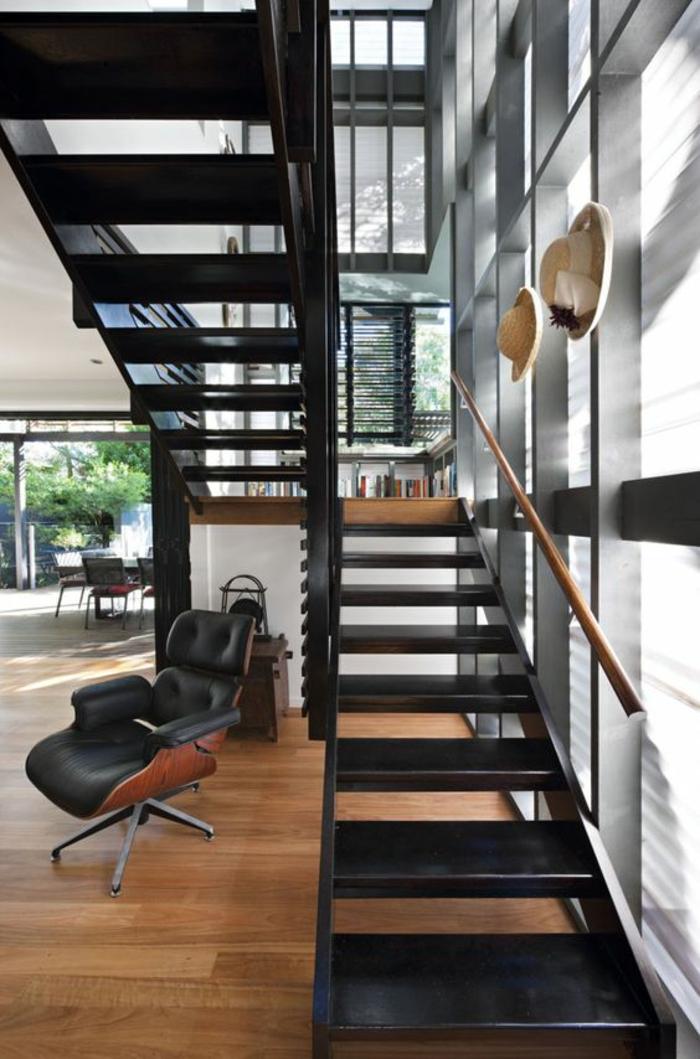 escalier design, escalier moderne, escalier interieur en métal noir, décor industriel avec deux chapeaux comme décoration sur les éléments en métal, marches larges et grandes, parquet en PVC, grandes fenêtres lumineuses, fauteuil à roulettes en noir et marron