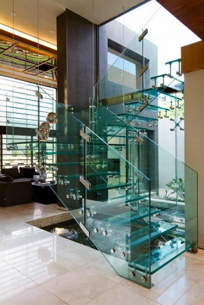 escalier moderne avec garde corps en verre transparent, marches en verre trempé au reflets bleutés, sol avec carrelage beige