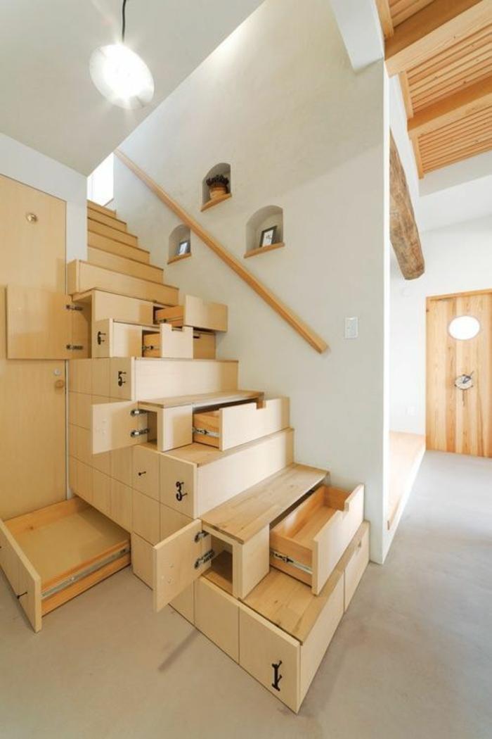 escalier bois clair, avec des marches qui contiennent des tiroirs dans leur intérieur, poignée simple et minimaliste, sans ornements, en bois clair, sol avec des carrelages blancs, plafond décoré avec faux plafond de poutres en bois clair