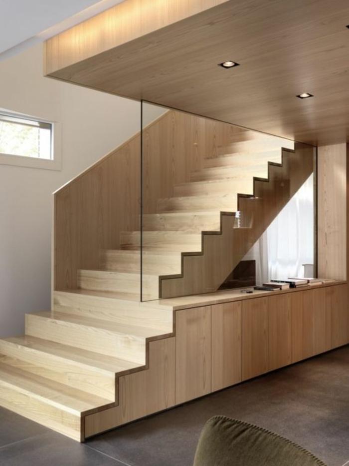 escalier bois clair avec des marches larges, faux plafond massif illuminé par des petits corps luminaires en forme carrée, carrelage gris clair, meuble en velours vert olive