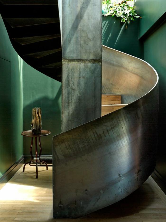 escalier moderne métal, murs de la pièce en vert, escalier en colimaçon, petite table ronde basse en fer forgé, avec vase arty en pierre, sol avec revetement en bois PVC clair
