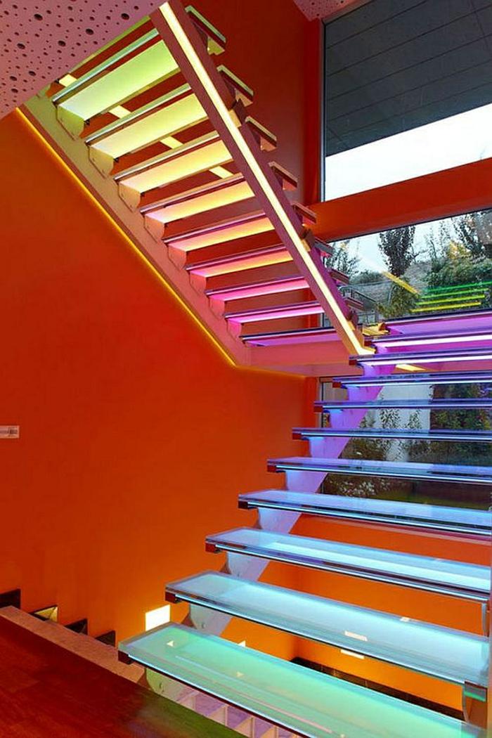 escalier moderne avec des marches lumineuses dans des couleurs fluorescentes, murs escalier en orange, sol en revetement bois PVC en couleur cerise