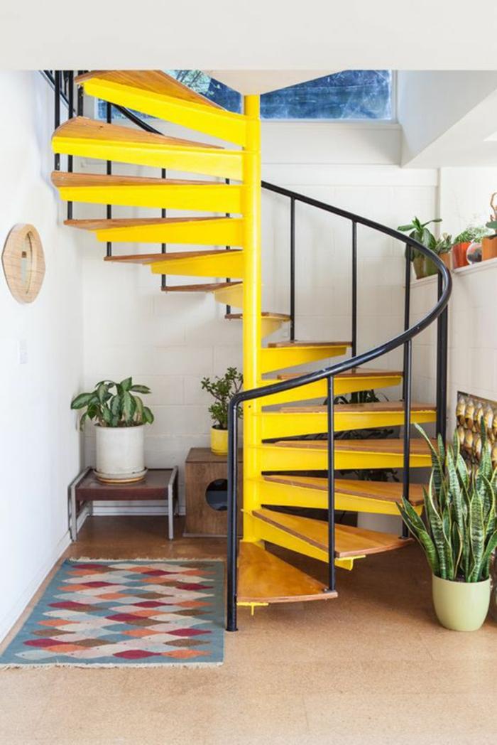 escalier design en métal jaune motif coquillage, avec garde corps en métal noir, petit tapis rectangulaire en couleurs pastels, deux grands pots blancs avec des plantes vertes exotiques