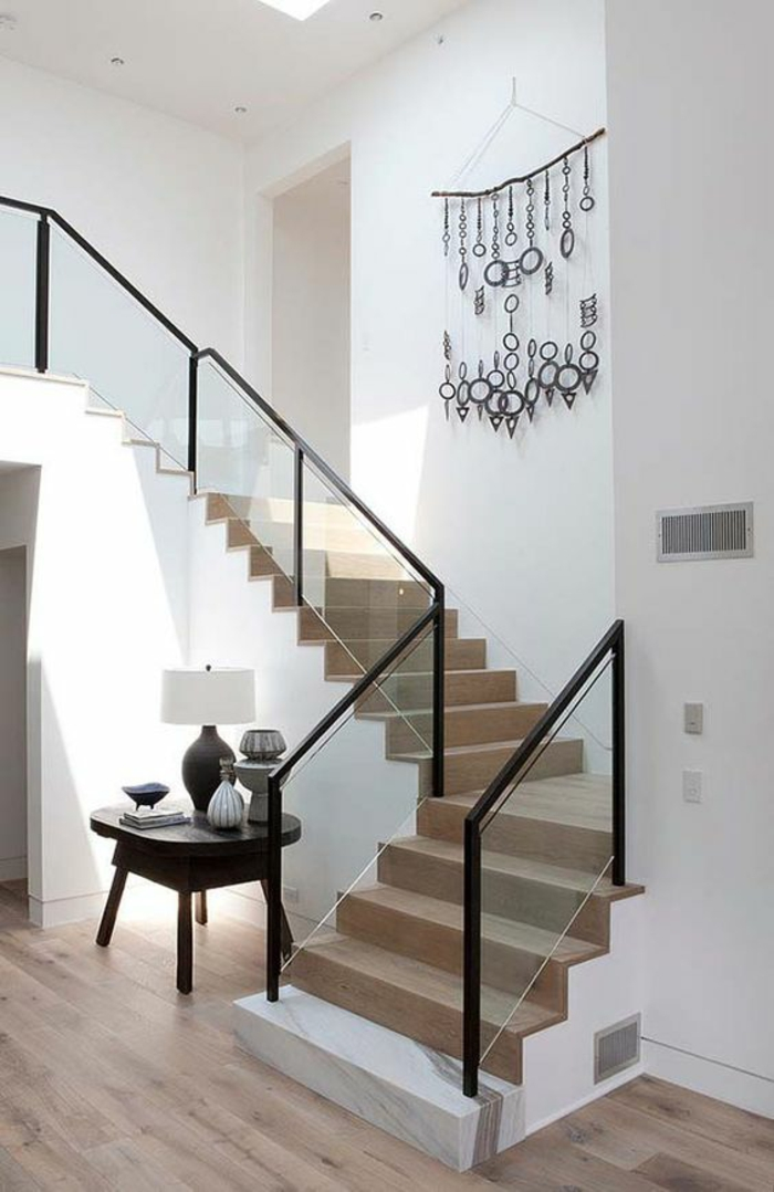 escalier flin en bois clair avec base blanche, garde corps en métal noir et verre blanc transparent, petite table carrée noire avec lampadaire avec abat-jour blanc, murs tout blancs