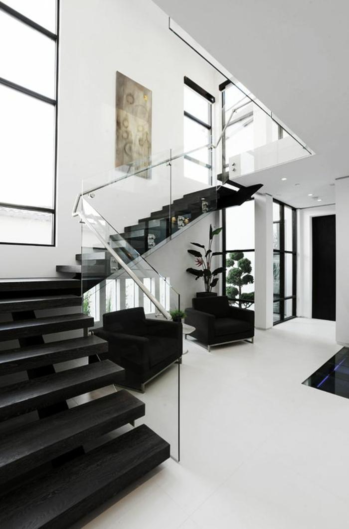escalier moderne, escalier flin, escalier interieur, marches noires, garde corps en plexiglass transparent à peine visible, carrelage blanc au sol, grande fenêtre haute, divisée en petites rectangles par des lignes métalliques noires, tableau en couleurs pastels