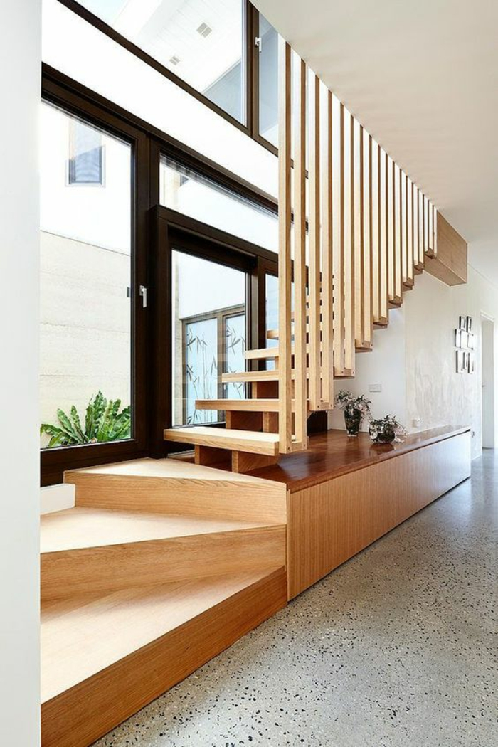 escalier limon central double, imitation bois clair, garde corps en forme de rayures tout au long des marches, sol en blanc et noir