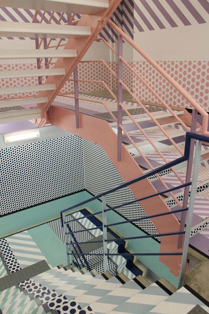 escalier design avec ds marches en rayures colorées, avec des motifs petits et grands pois, garde corps en diverses couleurs pastels, rose et bleu, avec des zones accentuées en bleu marine