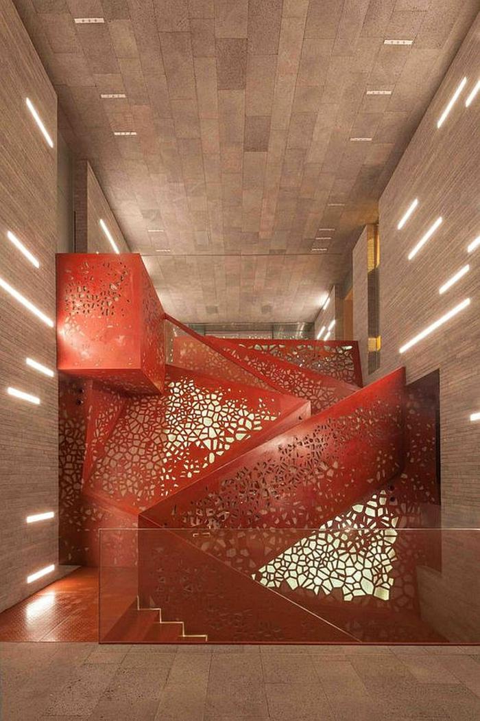 escalier design avec garde corps en couleur rouge, décoré de motifs ajourés, marches qui montent et qui descendent, murs et plafond en couleur beige nuances claires et foncées