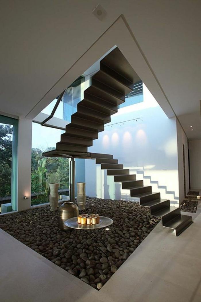 escalier design, escalier moderne, avec des marches en métal gris foncé, cheminée ronde en métal à la base de l'escalier, grand carré plein de cailloux noirs et blancs, deux grandes vases blancs, carrelage beige