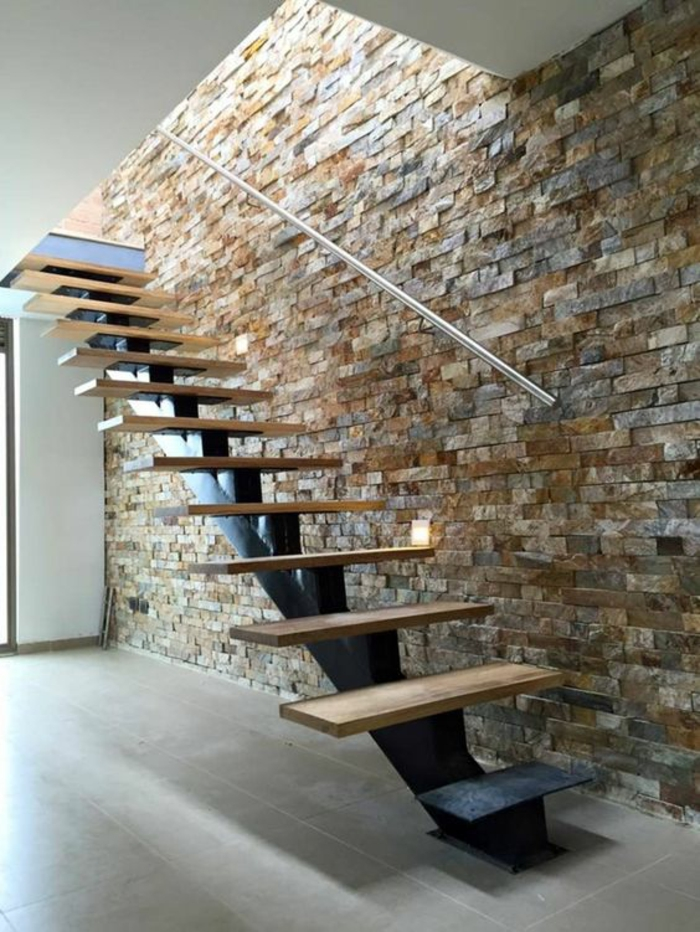 escalier moderne, escalier design, avec des marches en bois clair sur base métallique noire, murs en pierres multicolores, en couleurs claires, simple poignée minimaliste en couleur argent