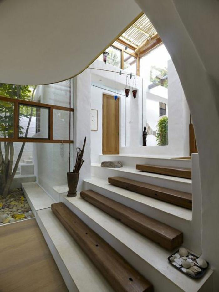 escalier design avec base en blanc et partie en bois couleur foncée, cailloux décoratifs, porte-parapluie, ambiance ethno chic