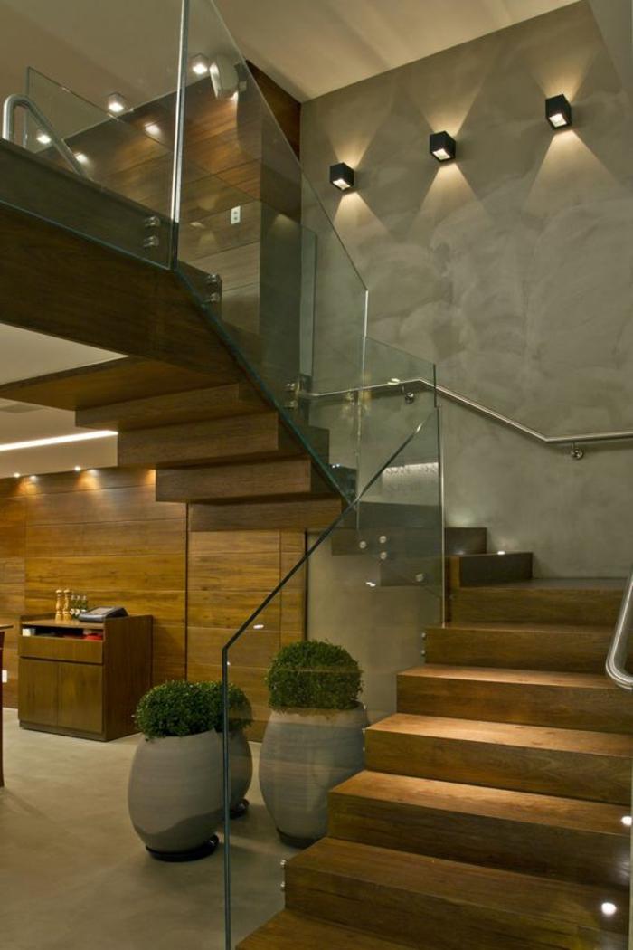 flin escalier avec garde corps en verre transparent, mur avec des appliques carrées en métal noir, murs en pierre grise, style industriel, trois grands pots en pierre blanche avec des plantes vertes