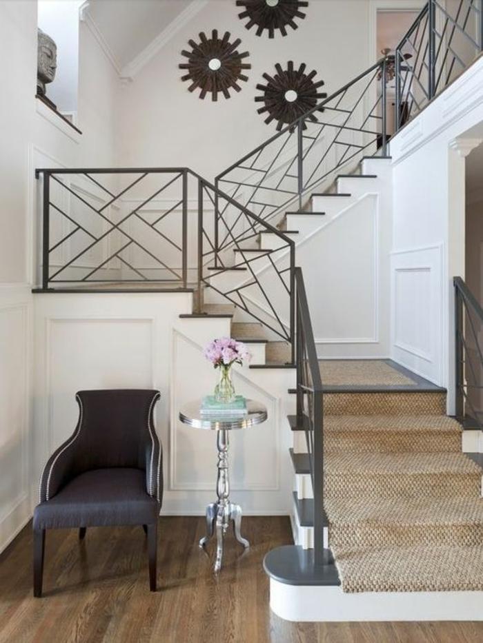 escalier design en métal noir avec des motifs formes géométriques, éléments décoratifs pour le mur en forme de trois soleils en métal aluminium, fauteuil gris anthracite en style néo-classicisme, escaliers initiaux recouverts de tapis roulant beige