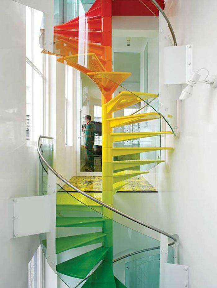 escalier design dans les couleurs de l'arc en ciel, marches en rouge, orange, jaune, vert, style escalier escargot, dans un établissement en style industriel