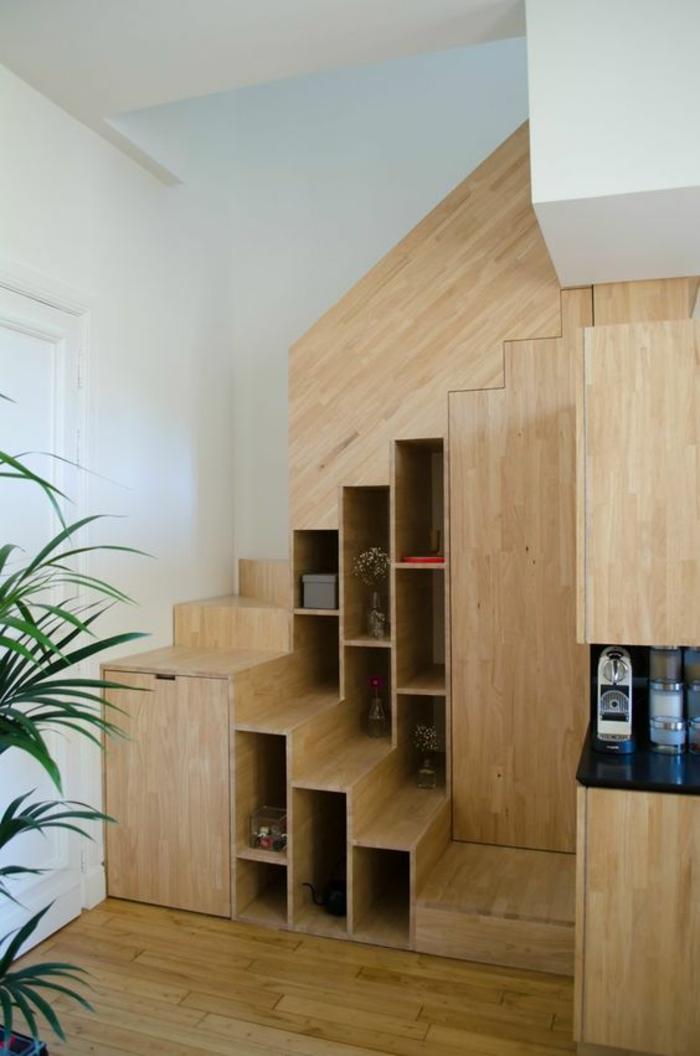 escalier design en bois PVC clair avec bibliothèque à plusieurs niveaux insérée, sol recouvert de parquet en bois clair, grande plante verte palmier dans un pot, plafond blanc,