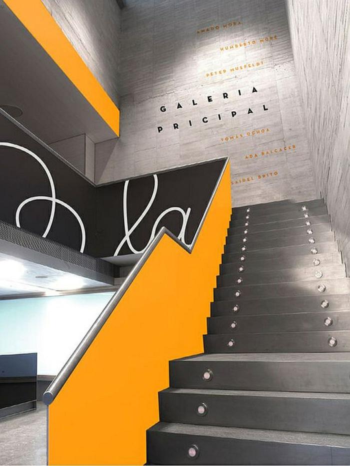 escalier design en gris anthracite et garde corps en jaune dans une galerie d'art, marches illuminées par des petits corps lumineux, disposés de manière régulière par deux sur la longueur de la marche