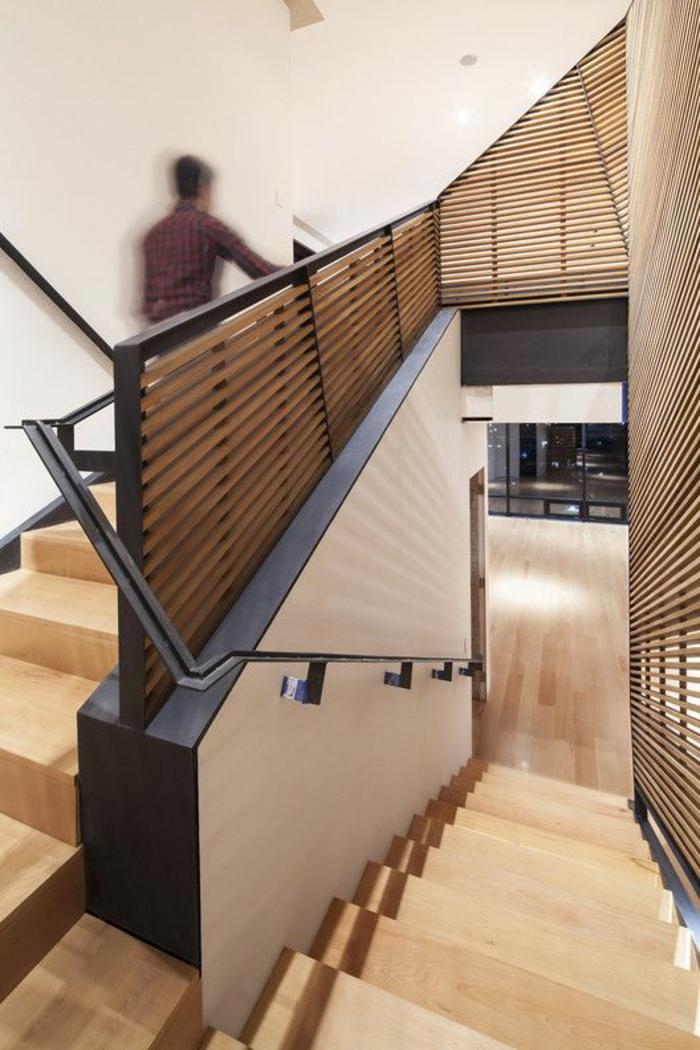 escalier design en bois clair, avec garde corps en métal noir, murs en beige, garde corps avec des bandes fines de bois clair