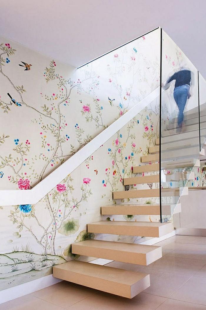 escalier design avec des marches suspendues en bois clair, avec garde corps en verre blanc et poignée en métal blanc couleur argent