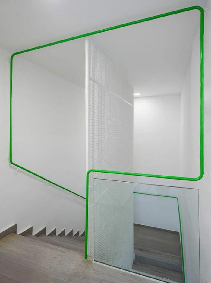 escalier interieur en blanc et vert flashy avec forme géométrique et des marches en gris clair, avec des nuances taupe, garde corps en métal blanc perforé