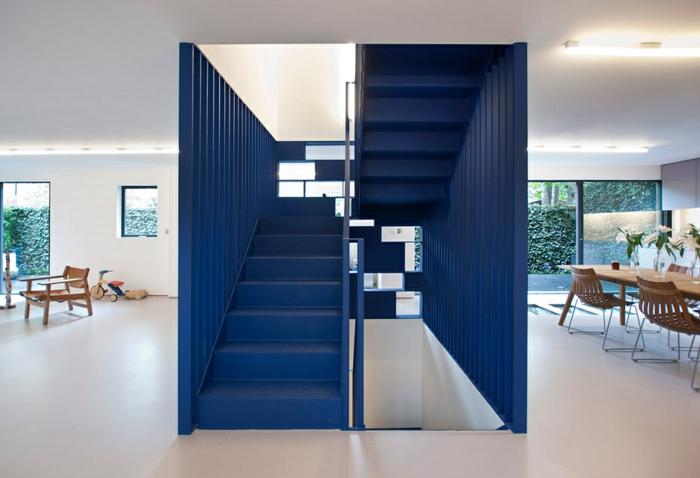 escalier design en bleu marin avec revetement en métal en forme de cube, sol avec carrelage beige luisant, table et chaises en bois clair