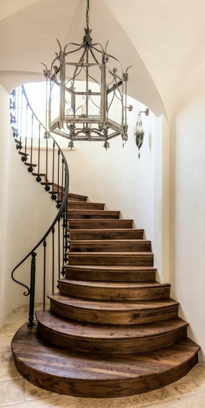 escalier design en bois marron foncé, avec lustre en métal blanc et verre, style château de la Renaissance française, garde corps en métal noir en forme ondulante