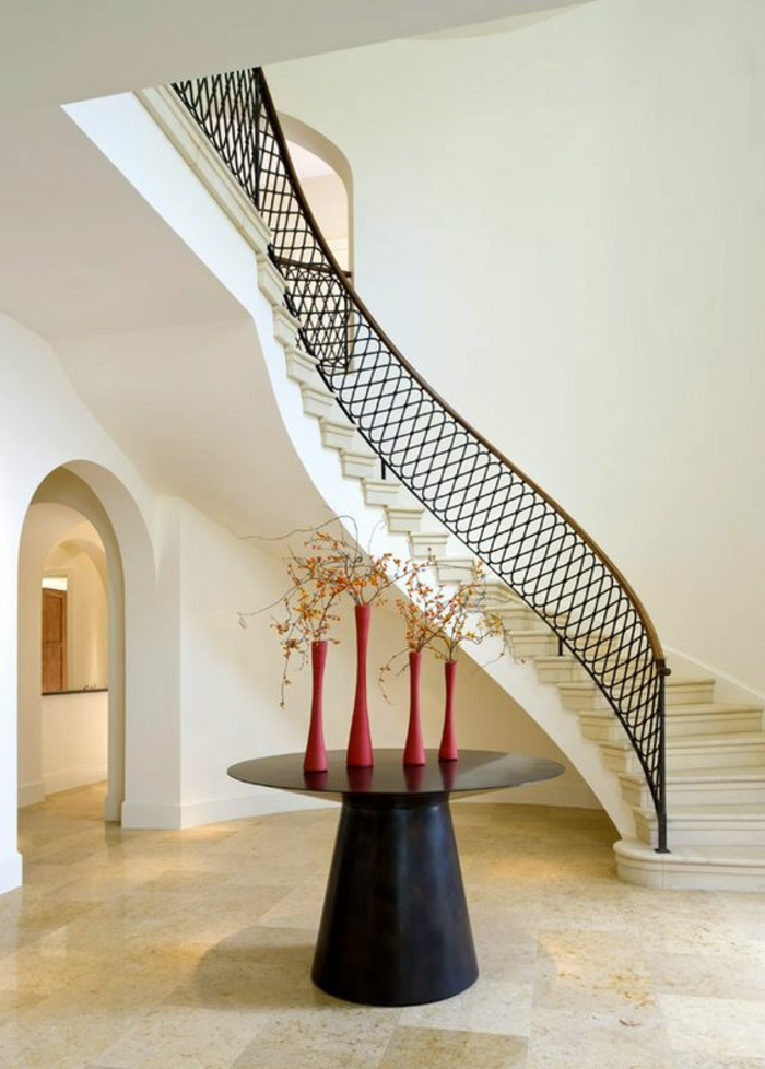 escalier design, escalier interieur en forme ondulante, garde corps en métal noir, sol recouvert de grandes dalles en beige et blanc, table d'entrée ronde et noire, avec quatre vases rouges étroites avec des plantes séchées décoratives
