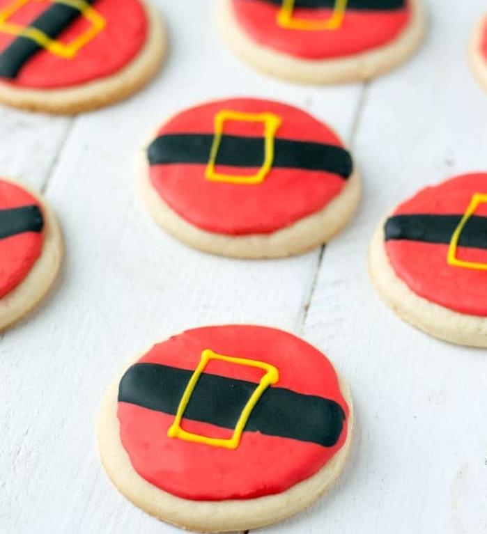 sables de noel, simples biscuits au beurre, avec glaçage rouge, noir et jaune, imitation costume père noel