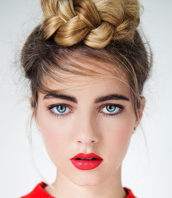 exemple de coiffure pour noel simple, chignon tressé, mèches libres et franges sur le côté, pull rouge