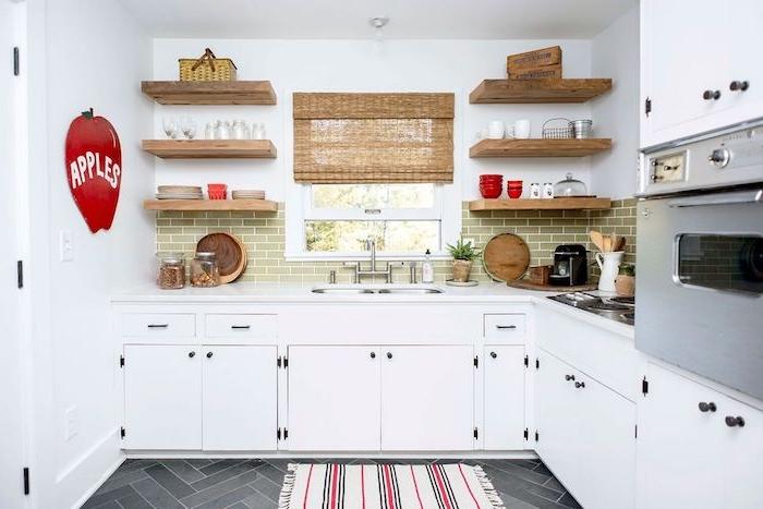exemple de cuisine campagne chic avec facade blanche et credence carrelage vert, etageres en bois rustiques, sol carrelage gris, store en bambou, sticker pomme rouge