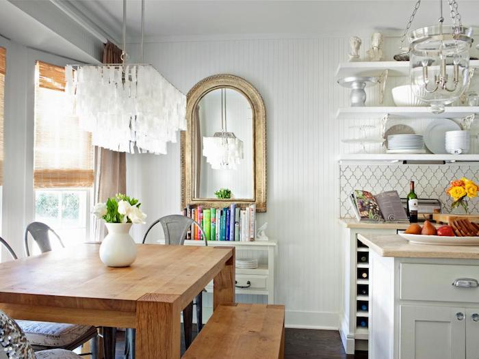 exemple de cuisine rénovée blanche avec ilot central et plusieurs etageres blanches avec vaisselle blanche, table et banc en bois, suspension et vase blanc