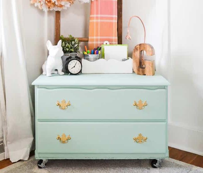 meuble repeint, petite table d appoint repeinte en bleu ciel avec des tiroirs et accessoires decoratifs rangés dessus, poignées dorées, echelle decorative en bois