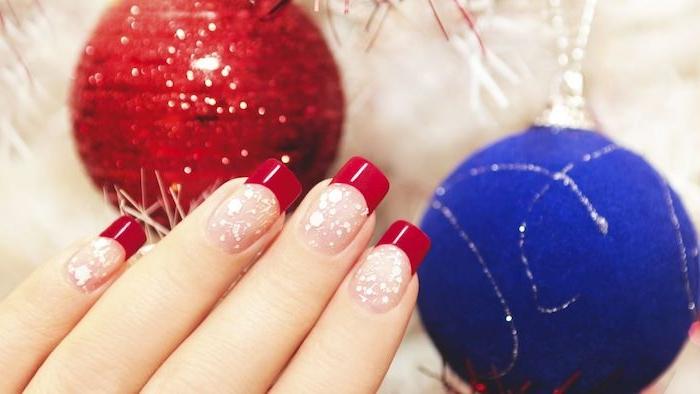 nail art rouge pour noel, vernis à ongles nude, couleur rose, petits pois blancs et bouts d ongles rouges, boule de noel rouge et bleue