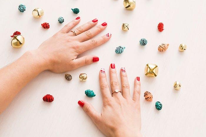 nail art rouge pour noel, vernis à ongles rouges et motif canne de bonbon menthe poivrée, rayures blanches et rouges, clochettes, petites pommes de pin