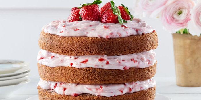 exemple de recette de glacage de fromage à la crème et fraises pour faire un gâteau à trois étages, décoration de fraises rouges dessus