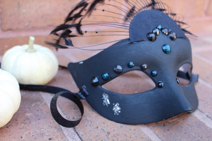 masque carnaval maternelle, idée diy pour masque de fête, customiser un masque blanc avec couche de peinture noire et plumes