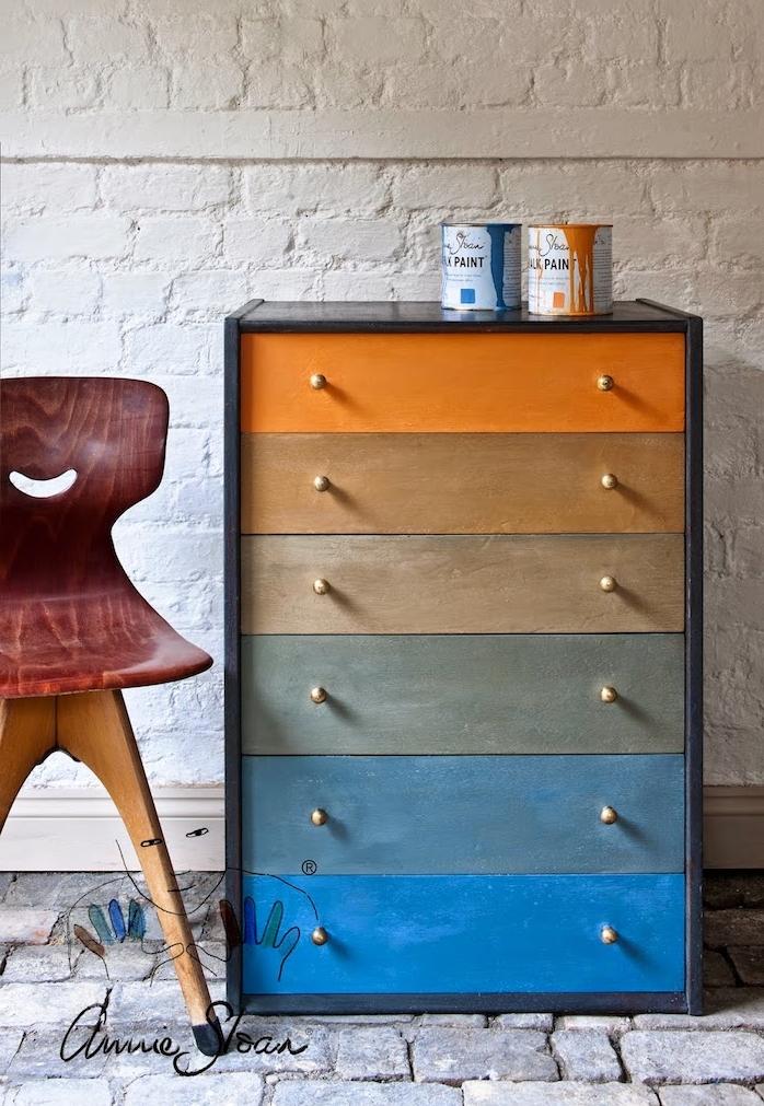 repeindre un meuble en bois, facade de tiroirs à effet ombré, peinture couleur orange, marron, gris et bleu, mur en briques blanchis, chaise vintage