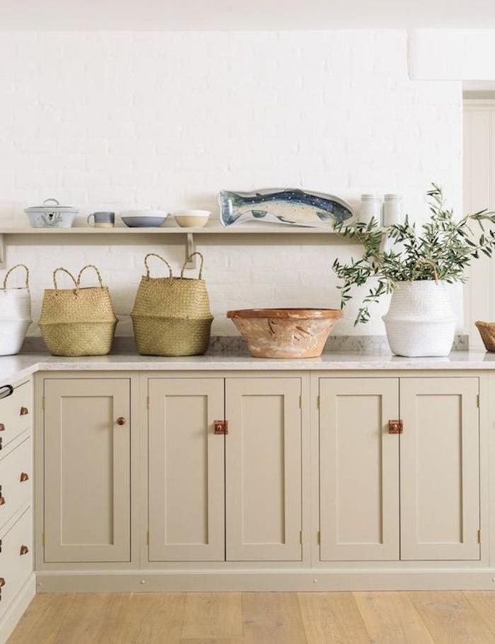 amenagement cuisine avec façade couleur taupe clair, plan de travail marbre, paniers de rangement rustiques, étagère ouverte avec vaisselle