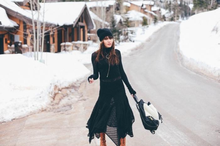 look total noir avec pantalon slim noir porté par dessus blouse et tunique noire, coiffure de cheveux brun avec frange
