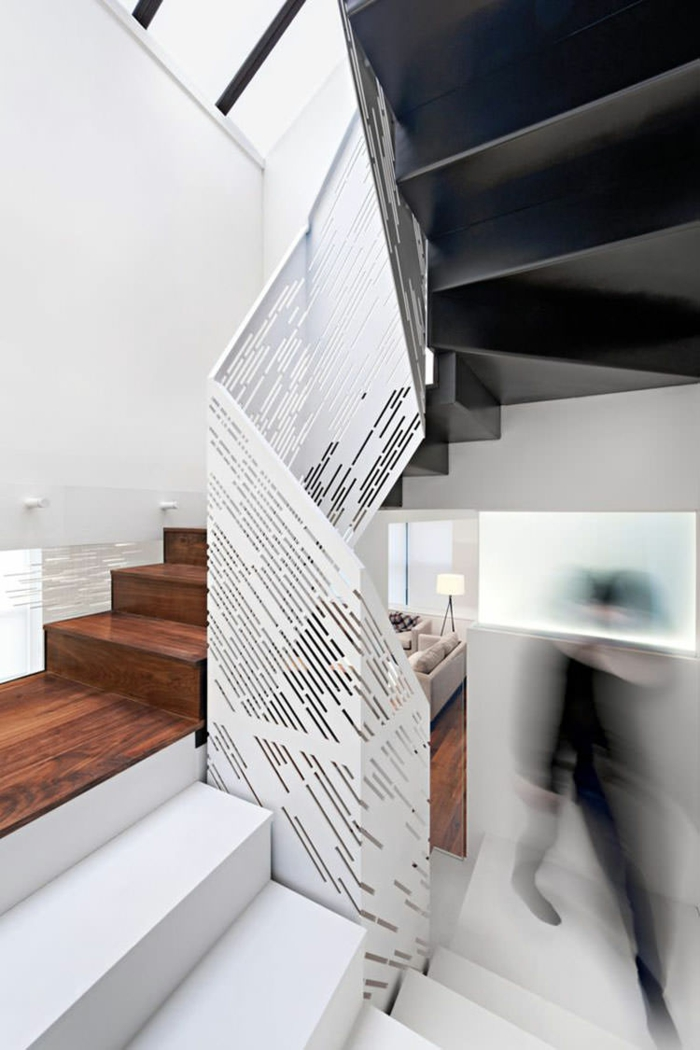 escalier bois en couleur cerise avec des marches hautes et massives, garde corps en métal blanc avec effet de spirale aux motifs ajourés, une partie des marches en blanc
