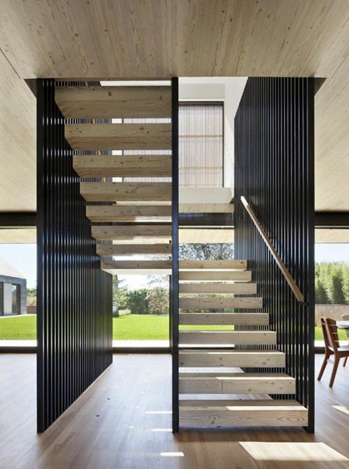 escalier interne, escalier design, en métal noir et escaliers en pierre blanche, plafond en pierre grise, sol recouvert de parquet PVC en nuances beiges et marron clair