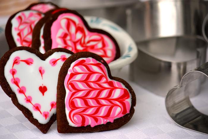 biscuits au chocolat au glacage sucre glace rouge et blanc effet marbre, sablés en forme de coeur pour saint valentin